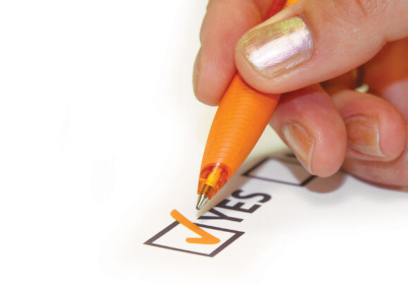 """fingers holding a pen ticking off a """"YES"""" box (Photo by yarranz from FreeImages)"""